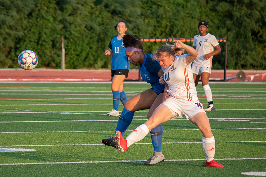 Battling to keep control of the ball, Junior Kayley Pedersen passes to a teammate.
