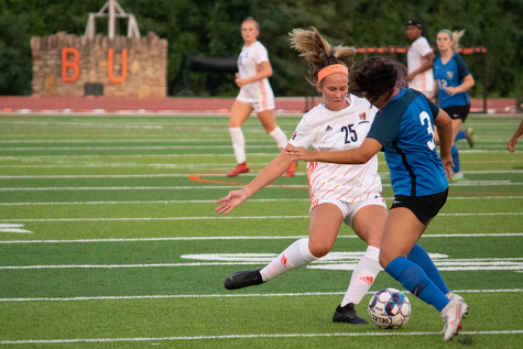 Passing to a teammate, Freshman Emma Schieber advances the ball in the first game of the season.