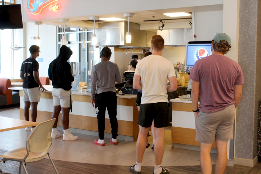 The lack of Cafe workers causes a delay as students wait in line for their meals during a lunch rush.
