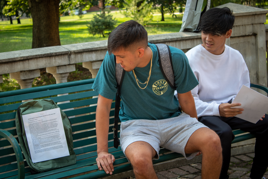 Senior Asiel Flores, and Sophomore Christain Nishi-Rivera take the time to read stories from the backpack campaign. Each backpack signifies a college or highschool aged student who lost their life to suicide.
