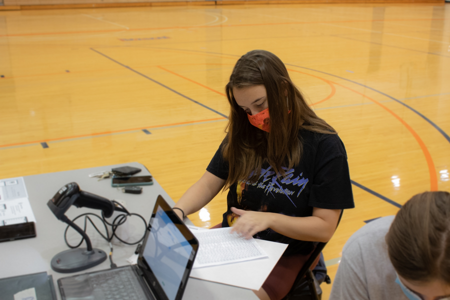 Senior and member of Pre-Health Club Chandler Davis flips through the list of those who signed up to donate.