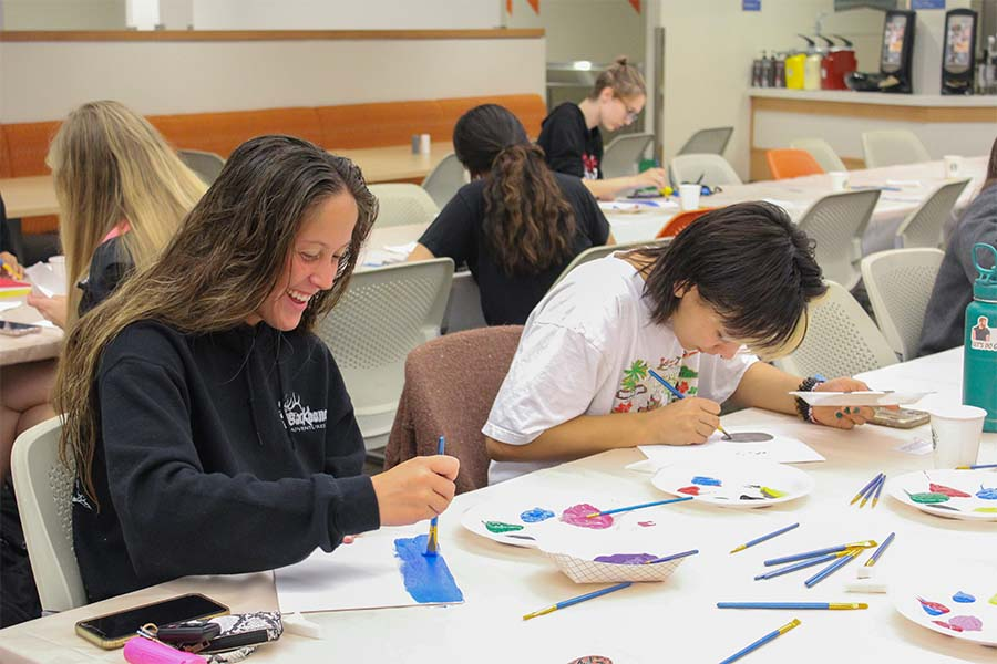 Freshman Cambrie Frame (left) and Sophomore Aaliyah Bueno (right) enjoy painting at SACs Paint Night on Sept 30.