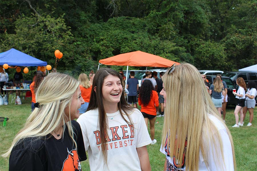 Sophomores Grayson Murphy (left), Katherine Heath (middle) and Taylor Brunton (right) share a laugh while waiting in line to receive food.
